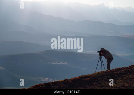 Silhouette of a lone photographer with camera and tri-pod shooting on the hills of Witsieshoek, Drakensberg, Kwazulu-Natal Province, South Africa - Stock Photo