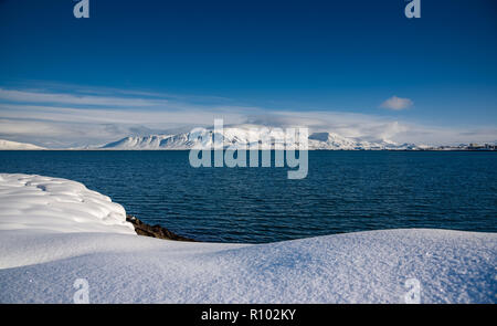 Amazing Iceland in winter - breathtaking scenery and frozen landscapes - snowy mountains at sunset - perfect winter scene on the ocean shore - Stock Photo