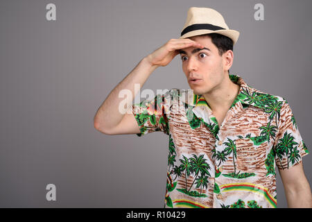 Young handsome tourist man ready for vacation against gray backg - Stock Photo