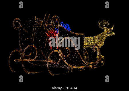 Christmas ilumination of a reindeer with sleigh carrying gifts in a garden outside