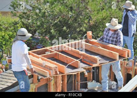 Dismantling a home for rebuilding an upstairs using immigrant labor - Stock Photo