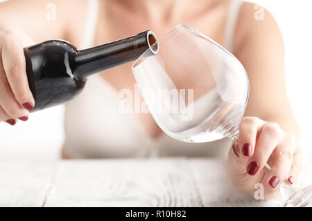 woman pouring herself a glass of red wine in the kitchen - Stock Photo