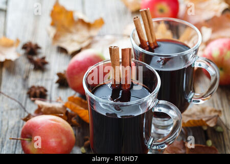 Hot mulled wine in glass on wooden table - Stock Photo