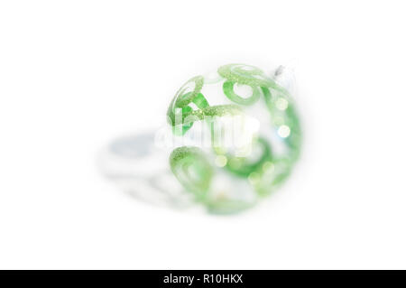 Blurred image of decorated clear glass Christmas bauble, white background - Stock Photo