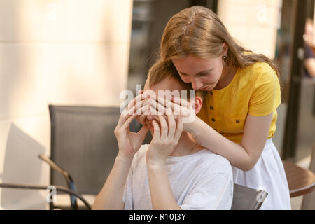 young woman covering a young man's eyes and smiling - Stock Photo