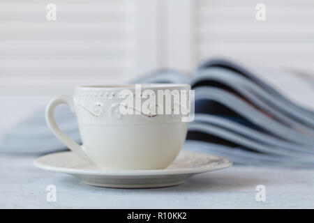 glossy magazine on a table, with coffee cup Very shallow depth of field - Stock Photo