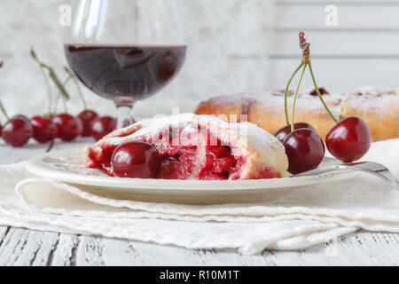 slice of cherry pie on a linen napkin with polka dots. A cake decorated with fresh cherries. Next to a glass of juice. From the series 'Homemade Cherr - Stock Photo