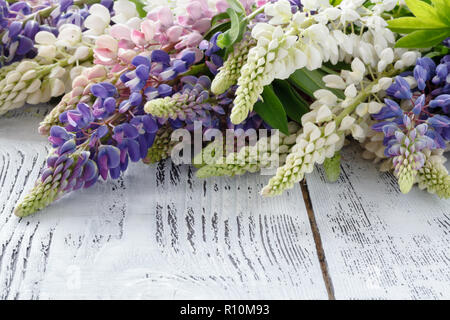 bouquet of the blue lupine flowers on a wooden table - Stock Photo