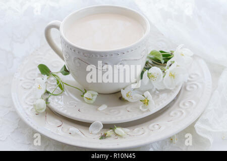 Masala tea chai latte homemade traditional Indian sweet milk with spices beverage in porcelain cup on wooden table background - Stock Photo