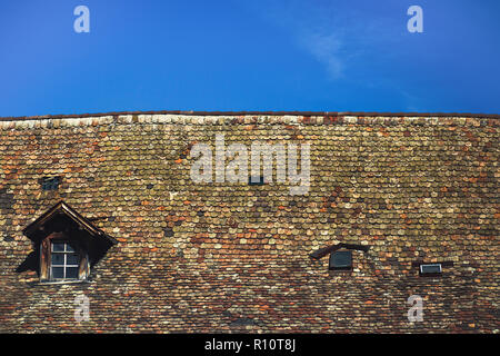 Old tile roof texture with small windows - Stock Photo