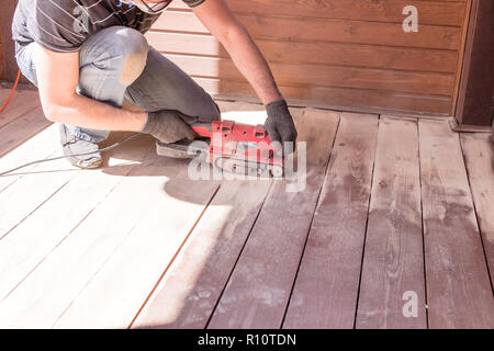 Sanding hardwood floor with the grinding machine. Repair in the apartment, country house,patio. Carpenter doing parquet wood floor polishing maintenance work by grinding machine.Copy space - Stock Photo