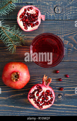 Ripe pomegranate fruit and a glass of pomegranate juice on wooden table. Healthy eating concept. - Stock Photo