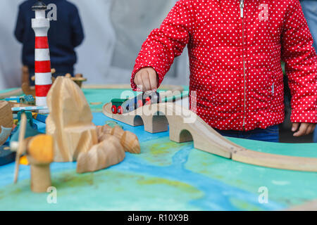 Little autistic boy playing with toy outdoor - Stock Photo