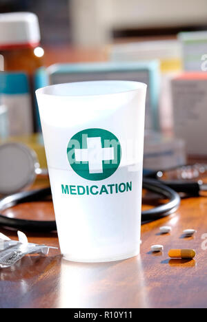plastic medication tumbler on doctor's table top - Stock Photo