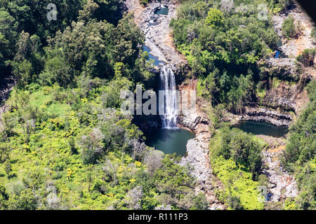 Aerial view of waterfall near Hilo, Hawaii. Water flows over rock into pool below; Rainforest crowds both banks. Second pool is nearby. - Stock Photo