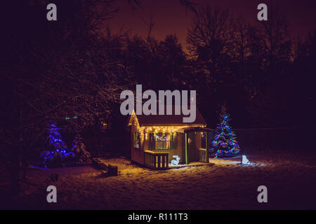 Wooden painted yellow private children`s play house in home garden, decorated with Christmas LED string lights outdoors in cold winder night. Decorate - Stock Photo