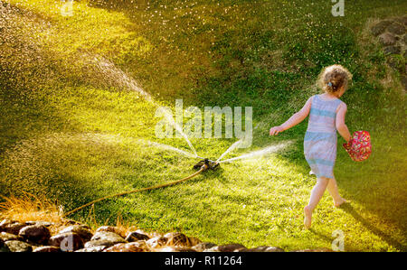 Irrigation sprinkler device for irrigation of home lawn, grass working and happy playful girl running through garden sprinkler summer night. - Stock Photo