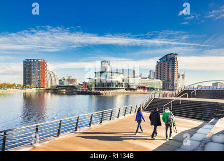 2 November 2018: Salford Quays, Manchester, UK -  Three young tourists strolling beside the Manchester Ship Canal. - Stock Photo