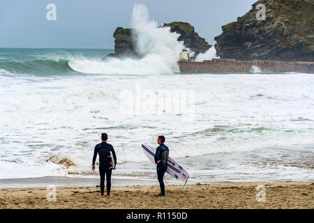 Surfers stand talking as giant waves batter the harbour walls and cliff edges. - Stock Photo