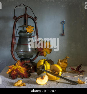 still life with quince, autumn leaves and kerosene lamp. vitamins. pick ripe fruit. vintage - Stock Photo