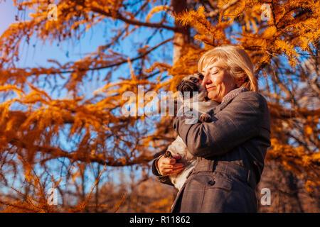 Master walking pug dog in autumn park. Happy woman hugging pet. - Stock Photo