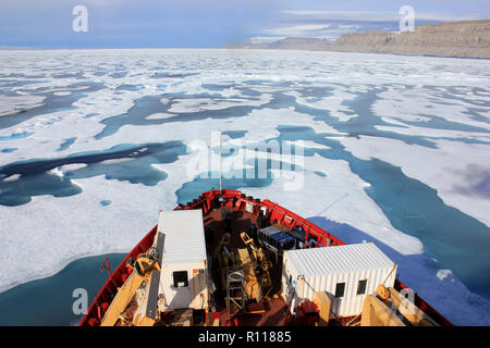 Scientist at the prow of the CCGS Amundsen as she breaks through the ice in Lancaster Sound, Arctic Canada - Stock Photo