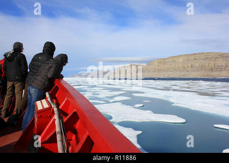 Scientists at the prow of the CCGS Amundsen as she breaks through the ice in Lancaster Sound, Arctic Canada - Stock Photo