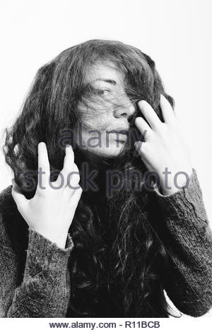 Back and white portrait of a woman posing against a white background - Stock Photo