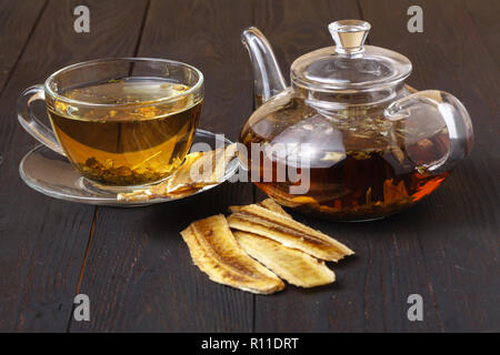 Sun-dried banana,dried banana with tea on wood background - Stock Photo