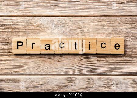 practice word written on wood block. practice text on table, concept. - Stock Photo