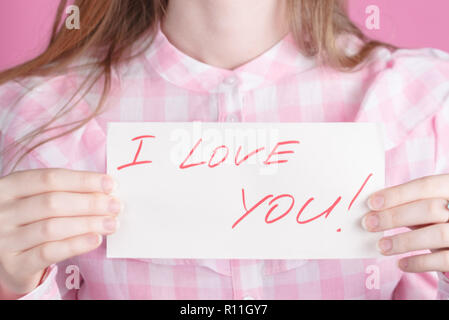 note in the hands with the words I love you - Stock Photo