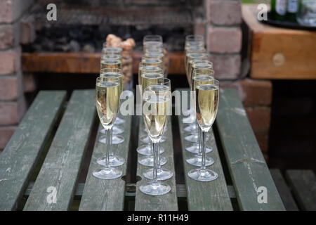 Three lines of champagne in glasses on a picnic table - Stock Photo