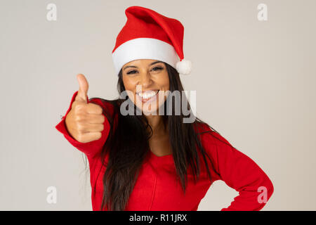 Cheerful beautiful and smiling young woman in santa hat and red sweater smiling playful and holding copy space over gray background in merry christmas - Stock Photo