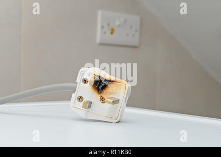 Burned 250V uk style socket and converter. Improper use of AC Power Plugs and Sockets cause of short circuit and fires at home - Stock Photo