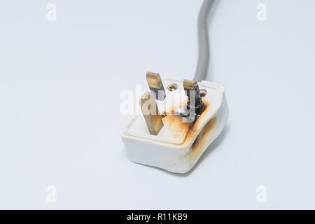 Burned 250V uk style socket and converter isolated on white. Improper use of AC Power Plugs and Sockets cause of short circuit and fires at home - Stock Photo