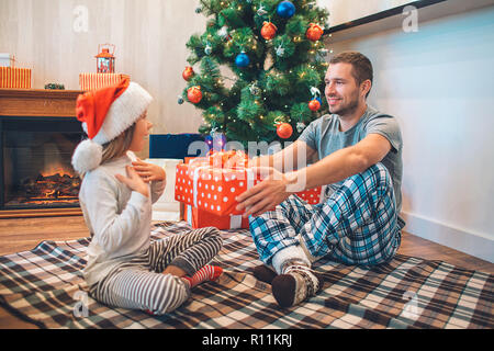 Lovely picture of father giving gift to his daughter. She is amazed. Girl points on herself and looks at father. He is happy to give her present. They - Stock Photo