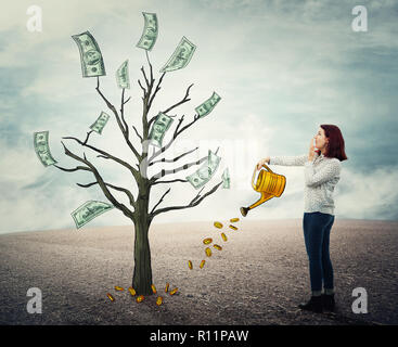 Young woman with a watering can pouring a plant with golden coins to raise a dollar bills money tree. Financial management, business growing, investme - Stock Photo