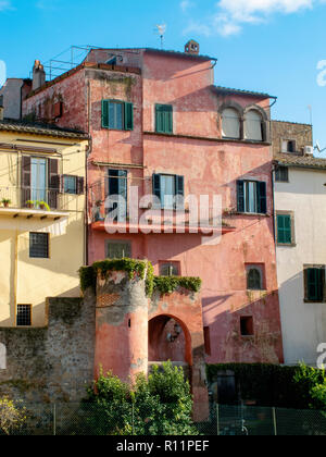 Ancient palace of red color in the medieval village of Tuscania (Italy) - Stock Photo