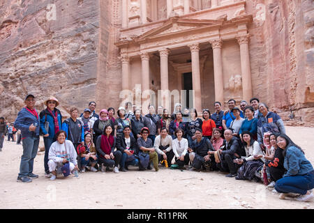 A group of tourists from Philippines poses for a photo in front of the Treasury, an elaborate temple in the ancient city of Petra in Jordan. - Stock Photo