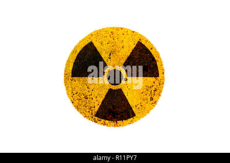 Round yellow and black radioactive (ionizing radiation) nuclear danger symbol on rusty metal grungy texture and isolated on white background. - Stock Photo
