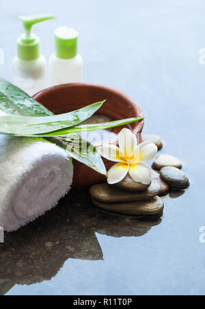 White Towel, yellow flowers, green leaves and cosmetics on dark marble background - Stock Photo