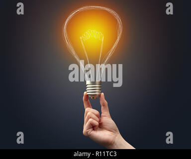 Hand holding light bulb on dark background. New idea concept - Stock Photo