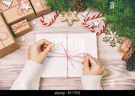 Many envelopes tied with rope. Close-up top view of famale hands with envelope. Pine cones and christmas decoration on old rustic vintage wooden table - Stock Photo