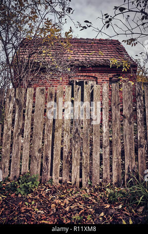 Old wooden fence in front of a spooky, abandoned house, color toning applied. - Stock Photo
