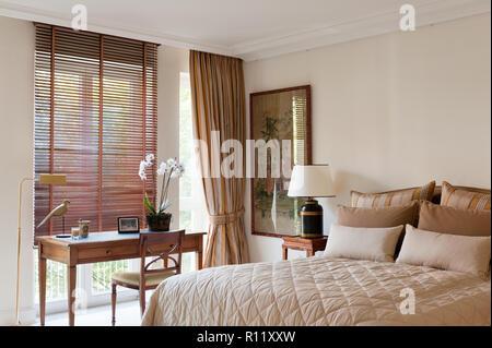 Desk by window in bedroom - Stock Photo