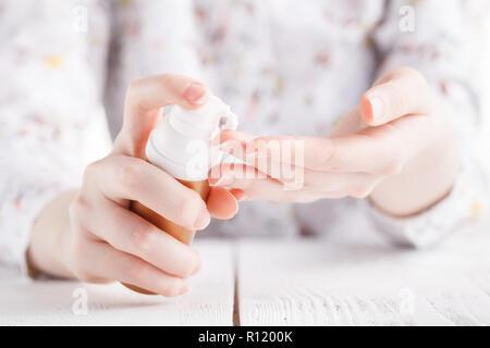 Young woman hands applying moisturizing cream to her skin - Stock Photo