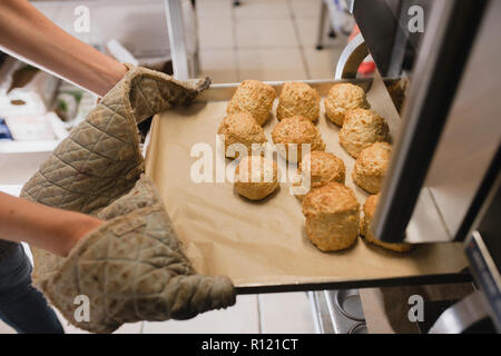 Unrecognisable person wearing oven gloves as they pull out a tray of scones from the oven. - Stock Photo