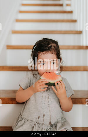 Girl enjoying watermelon on stairs - Stock Photo
