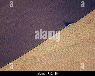 Aerial photo of a tractor ploughing a field in a countryside, country business concept. Plowing in autumn season, drone shot.