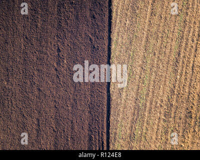 Aerial photo of a ploughed field in a countryside. Plowing in autumn season, drone shot from above. - Stock Photo
